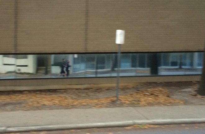 TJ and me running warmup laps - reflection of us in the window of a building.